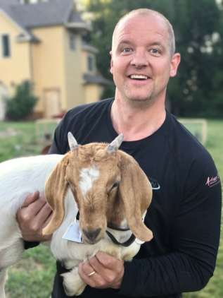 Matt Jensen carries the nanny goat into their pen
